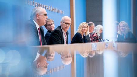 Sechs Menschen sitzen hinter einem großen Tisch.
