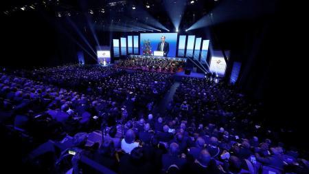 Ein Mann steht in einer großen Halle auf einer Bühne und spricht.