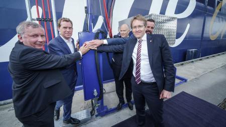 Ministerpräsident Daniel Günther steht mit vier anderen Männern vor einem Schiff und drückt einen Knopf.