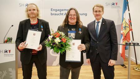 Drei Männer stehen nebeneinander, zwei von ihnen halten Urkunden in der Hand.
