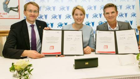 Zwei Männer und eine Frau sitzen am Tisch. Sie halten einen unterschriebenen Vertrag in die Kamera.