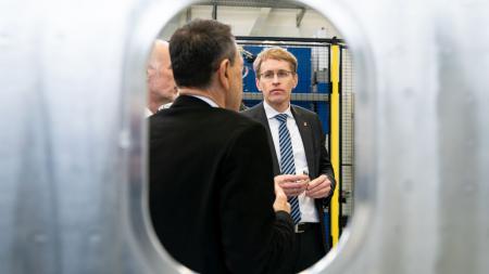 Drei Männer unterhalten sich in einer Werkshalle.