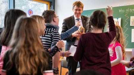 Ein Mann steht inmitten von Schülern und hält ein Kuscheltier in Form eines Erdmännchens in der Hand.