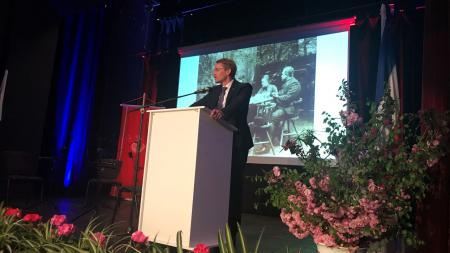 Ein Mann steht an einem Rednerportal. Hinter ihm wird ein schwarz-weißes Foto auf eine Leinwand projiziert.