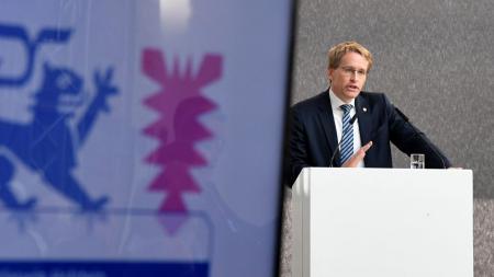 Ein Mann steht auf einer Bühne hinter einem Rednerpult.