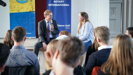 Ein Mann und eine junge Frau sitzen auf einer Bühne und unterhalten sich, vor ihnen sitzen Menschen.