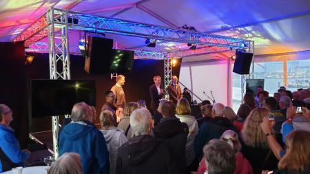 Ein Mann steht in einem großen Zelt auf einer Bühne und spricht in ein Mikrofon. Vor der Bühne stehen viele Menschen und hören ihm zu.
