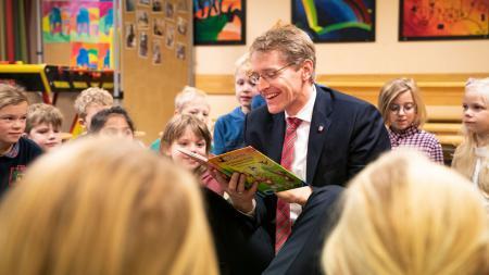 Ein Mann sitzt inmitten vieler Kinder und liest aus einem Buch.