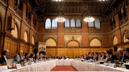 Großer Saal mit zur U-Form angeordneten Tischen an denen Menschen konferieren.