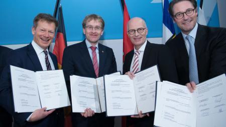Vier Männer lächeln in die Kamera und halten Vertragspapiere in den Händen.