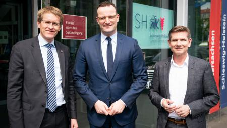 Ministerpräsident Daniel Günther steht neben zwei Männern vor der schleswig-holsteinischen Landesvertretung in Berlin.
