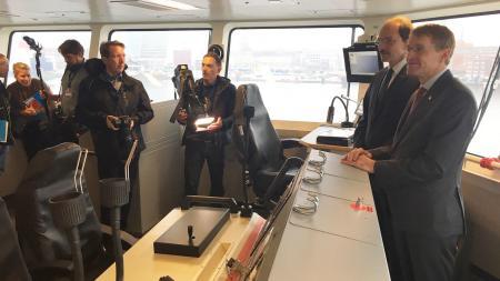 Zwei Männer stehen im Innenraum einen Schiffes hinter einem Schalter, vor ihnen sind Menschen mit Kameras.