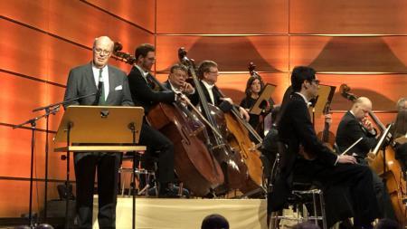 Innenminister Hans-Joachim Grote hält eine Rede am Rednerpult. Hinter ihm sitzen Mitglieder des Orchesters.