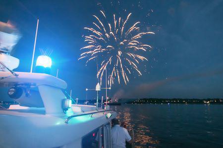 Ein Polizist blickt vom Boot auf das Feuerwerk