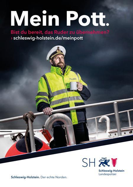 Kampagnenmotiv für die Wasserschutzpolizei; ein Polizist steht auf einem Schiff, in der Hand hällt er einen Becher Kaffee