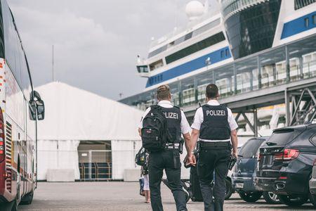Zwei Polizisten blicken auf ein Kreuzfahrtschiff