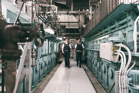 Zwei Polizisten gehen durch einen Maschinenraum