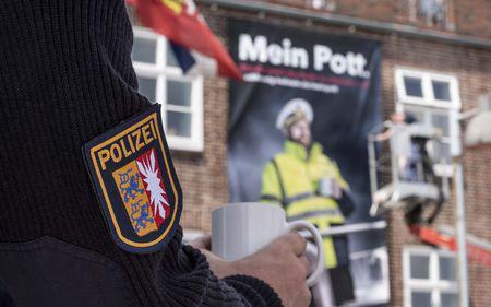 Ein Polizist steht mit einem Becher Kaffee auf einem Schiff, im Hintergrund das WSP Revier Kiel