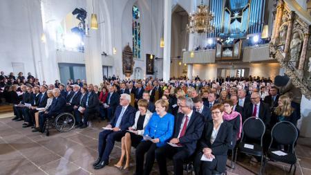 In einer Kirche sitzen viele Menschen auf Holzbänken.