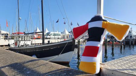Eine Plüschfigur in Form eines schwarz-rot-goldenen Leuchtturms lehnt an einer Hafenmauer. Im Hintergrund sind Schiffe zu sehen.