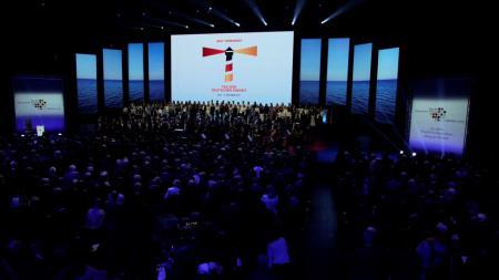 Eine Halle voller Menschen, auf mehreren Bannern sind das Logo des Tags der Deutschen Einheit zu sehen.