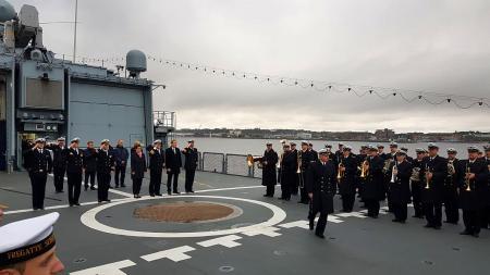 Auf dem Deck eines großen Militärschiffes stehen viele Menschen in Uniform.