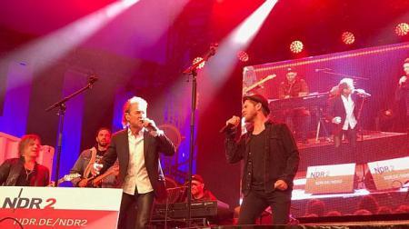 Zwei Männer stehen auf einer Bühne und singen in Mikrofone.