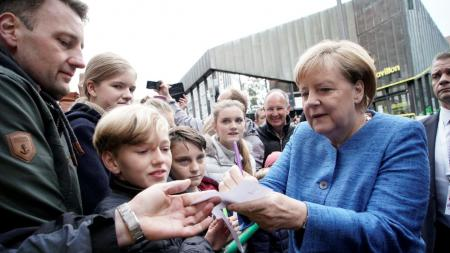 Eine Frau steht in einer Menschenmenge und gibt ein Autogramm.