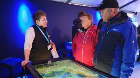 Eine Frau erklärt einem Besucherpaar die Darstellung auf einem Bildschirm.