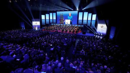 Eine Frau steht in einer großen Halle auf einer Bühne und spricht.