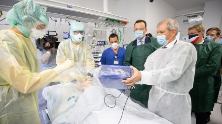 Menschen in Schutzkleidung stehen in einer Intensivstation um ein Bett herum und sprechen über medizinische Produkte.