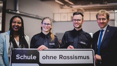 Vier Mensche halten gemeinsam ein Schild mit der Aufschrift Schule ohne Rassismus