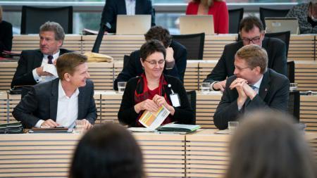 Drei Menschen sitzen in einem Plenarsaal nebeneinander und unterhalten sich. Im Hintergrund sind weitere Menschen zu sehen.