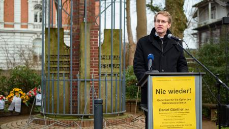 Ein Mann spricht an einem Rednerpult, an dem ein Plakat klebt mit der Aufschrift Nie wieder.