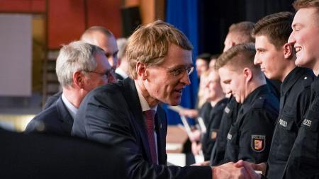 Ministerpräsident Daniel Günther schüttelt einem jungen Polizeibeamten die Hand.