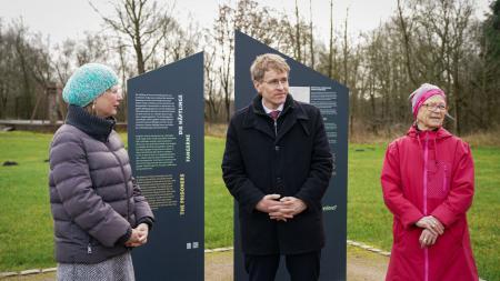 Zwei Frauen und ein Mann stehen vor zwei Gedenksäulen.