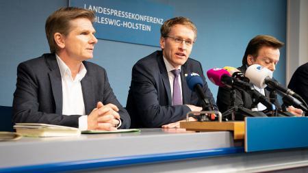Daniel Günther und Heiner Garg sitzen an einem Tisch, Günther spricht in mehrere Mikrofone.