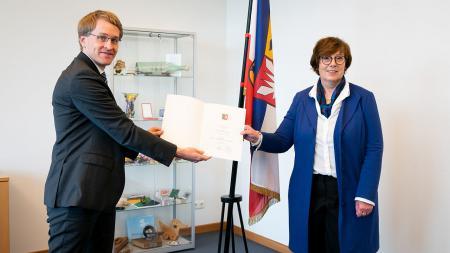 Ministerpräsident Günther überreicht eine Urkunde an Sabine Sütterlin-Waack