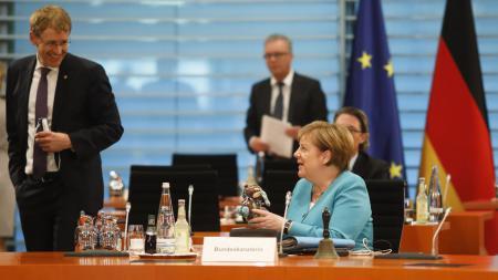 Ministerpräsident Daniel Günther steht neben Bundeskanzlerin Angela Merkel und lacht.