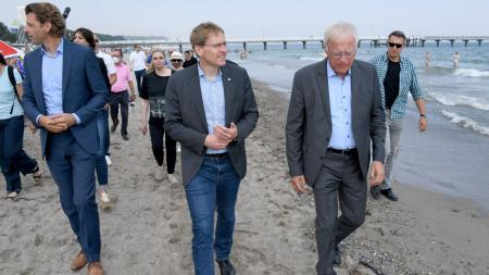 Ministerpräsident Daniel Günther, Landrat Reinhard Sager und Bürgermeister Robert Wagner laufen an einem Strand entlang.