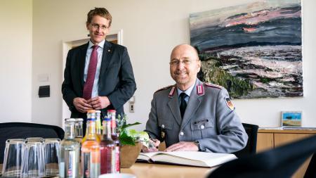 Oberst Schneider sitzt an einem Tisch und schreibt in das Gästebuch der Landesregierung. Hinter ihm steht Ministerpräsident Günther.
