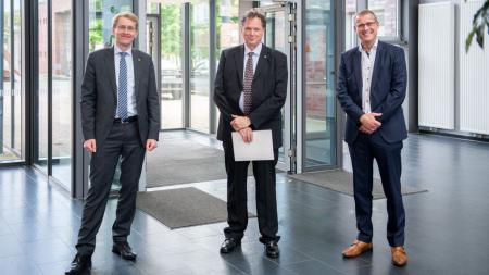 Daniel Günther, Udo Beer und Björn Christensen posieren im Foyer der Fachhochschule Kiel.