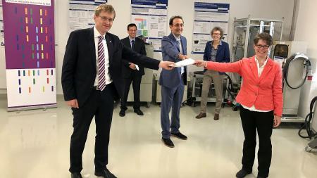 Ministerpräsident Günther überreicht einen Förderbescheid an die CAU-Wissenschaftler Dr. Marco Liserre und Dr. Sandra Hansen.