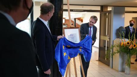 Ministerpräsident Daniel Günther enthüllt die Plakette des Schul-Sonderpreises.