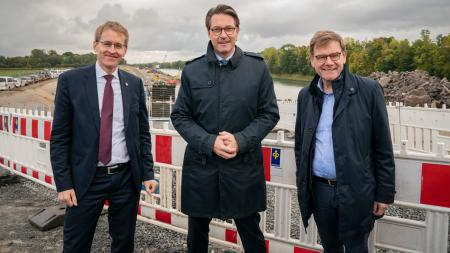 Ministerpräsident Daniel Günther und Bundesverkehrsminister Andreas Scheuer sowie Johann Wadephul stehen auf einer Baustelle. Im Hintergrund ist der Verlauf des Nord-Ostsee-Kanals zu erkennen.