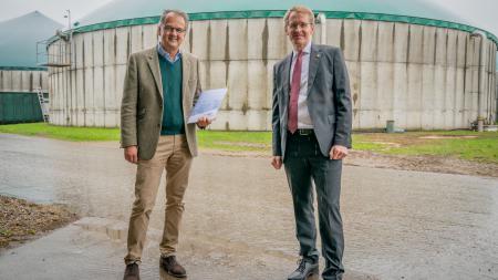 Ministerpräsident Daniel Günther und der Marienthal-Geschäftsführer Philip Klagges stehen nebeneinander. Klagges hält eine Mappe in den Händen, hinter den beiden ragt eine Biogasanlage in den Himmel.