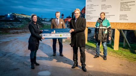 Auf der Baustelle vor dem Multimar Wattforum überreicht Ministerpräsident Günther der Projektleiterin Marén Bökamp-Hamkens den Förderbescheid. Dahinter stehen Michael Kruse (Leiter Nationalparkverwaltung) und Gerd Meurs-Scher (Leiter Multimar Wattforum).