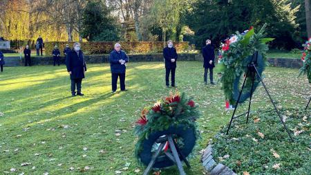 Ministerpräsident Günther, Klaus Schlie, Ekkehard Klug und Kiels Oberbürgermeister Ulf Kämpfer stehen auf einem Friedhof vor mehreren Kränzen.