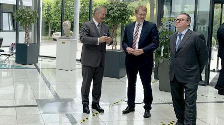 Ministerpräsident Daniel Günther steht mit zwei Vertretern der Firma Medac in einem Foyer.