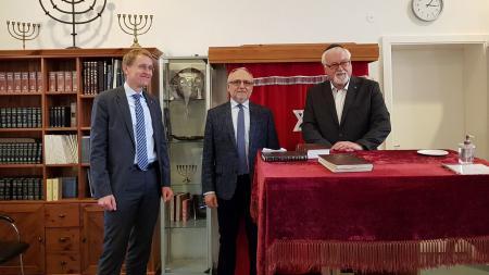 Ministerpräsident Daniel Günther, Igor Wolodarski und Peter Harry Carstensen stehen in einem Raum und lächeln in die Kamera.